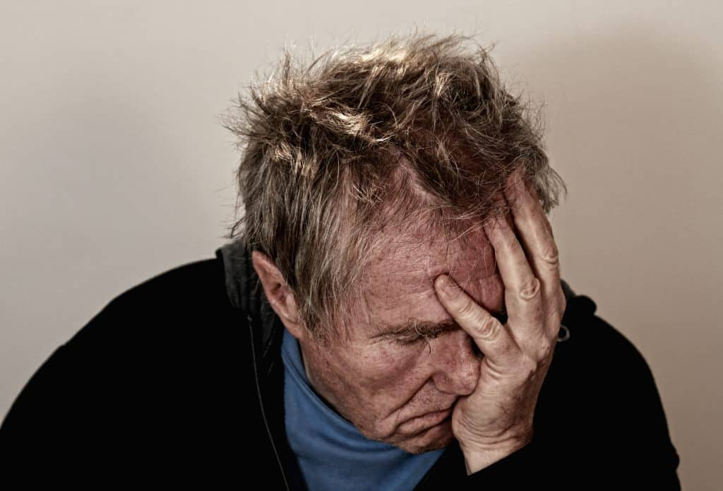 An older man with a headache from taking the wrong nootropic