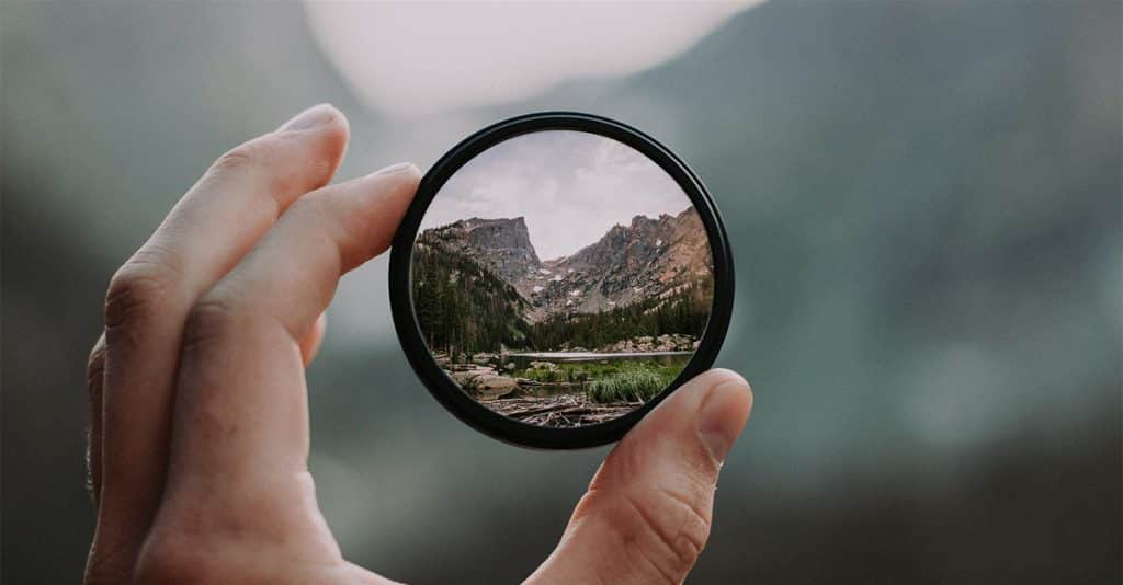 A hand holding a round mirror showing an image of a mountain